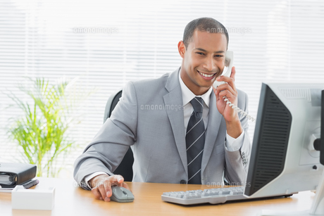 Businessman using computer and phone at office desk FYI00000001