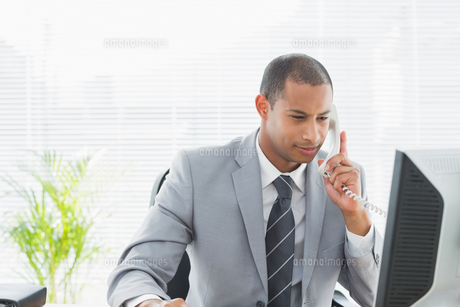 Businessman using computer and phone at office FYI00000002