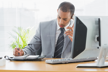 Businessman using computer and phone at office desk FYI00000003