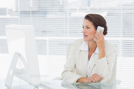 Businesswoman using computer and cellphone at desk FYI00000005