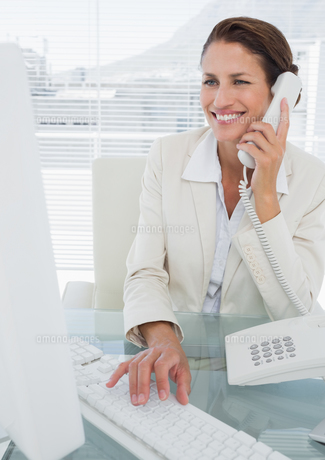 Smiling businesswoman using computer and phone FYI00000008