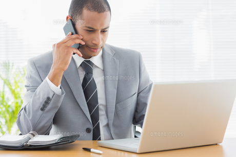 Businessman using laptop and cellphone at office FYI00000010