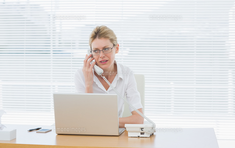 Businesswoman using laptop and phone at desk FYI00000014