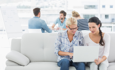 Women using laptop with colleagues in background at creative office FYI00000021