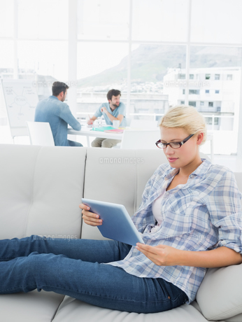 Woman using digital tablet with colleagues in background at creative office FYI00000022