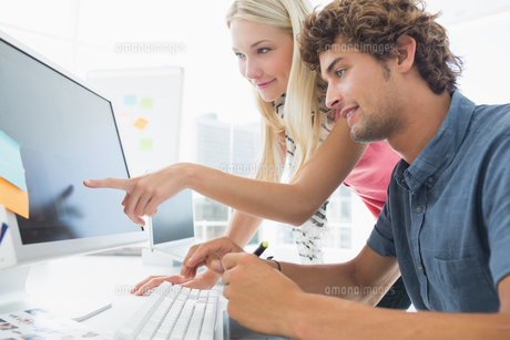 Casual couple using computer in office FYI00000043