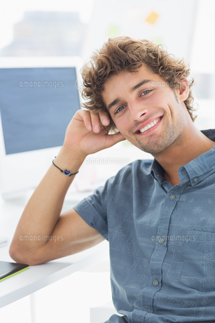 Smiling casual young man in office FYI00000045