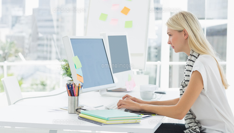 Casual young woman using computer in office FYI00000046