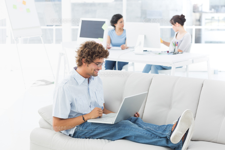 Man using laptop with colleagues at creative office FYI00000048