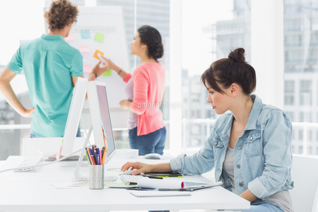 Casual woman using computer with colleagues behind in office FYI00000052
