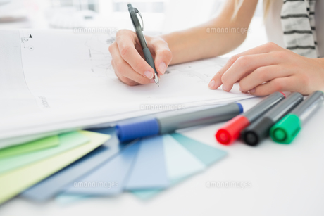 Artist drawing something on paper with pen at office FYI00000053