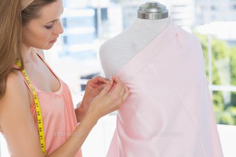 Beautiful female fashion designer working on pink fabric FYI00000055