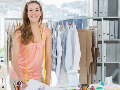 Smiling female fashion designer working in studio FYI00000056