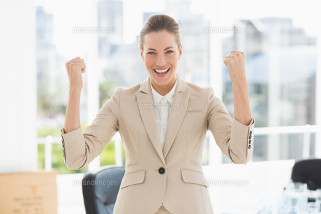Cheerful businesswoman clenching fists in office FYI00000063