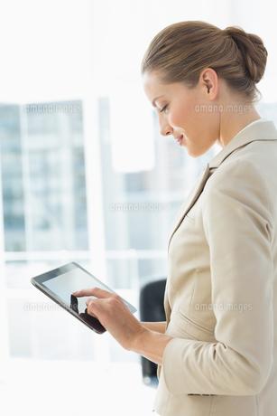 Beautiful businesswoman using digital tablet in office FYI00000070