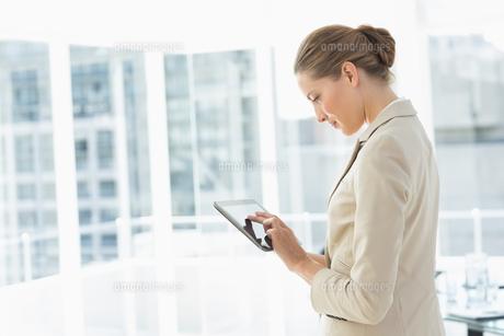 Beautiful businesswoman using digital tablet in office FYI00000071