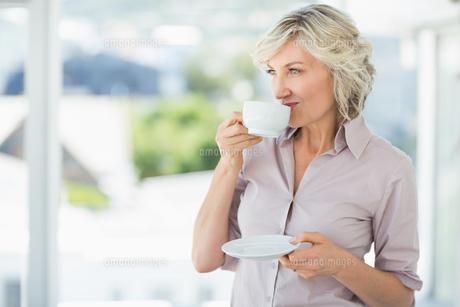 Smiling beautiful businesswoman drinking tea FYI00000078