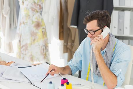 Smiling male fashion designer using phone in the studio FYI00000085