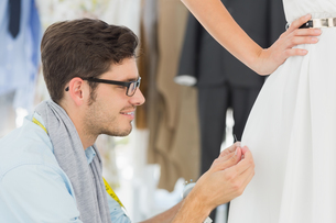 Male fashion designer adjusting dress on model FYI00000099