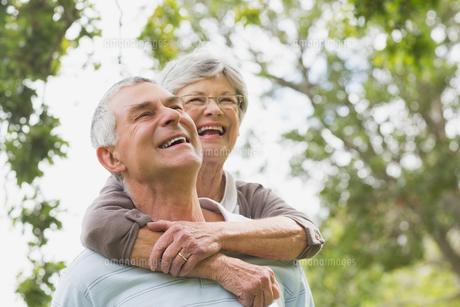 Senior woman embracing man from behind FYI00000147