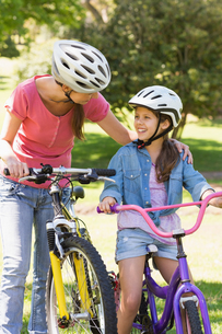 Smiling woman with her daughter riding bicycles FYI00000149