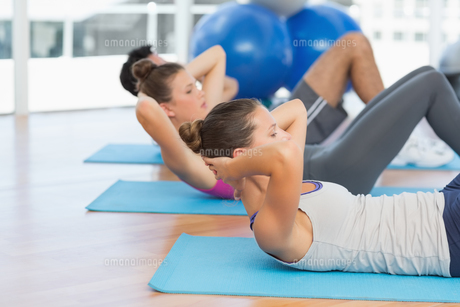 Determined people doing sit ups in fitness studio FYI00000184
