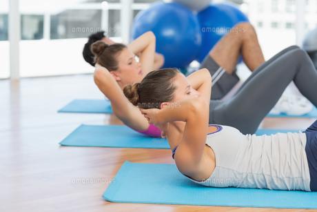 Determined people doing sit ups in fitness studioの素材 [FYI00000184]