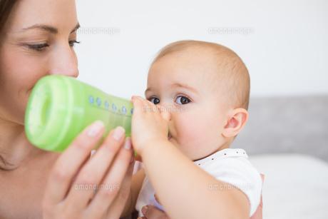 Mother feeding baby with milk bottle FYI00000524