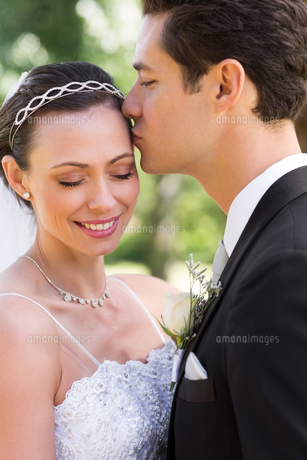 Groom kissing bride on head in gardenの素材 [FYI00000688]