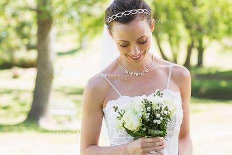 Bride looking at bouquet in garden FYI00000714