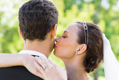 Young bride kissing groom on cheek FYI00000715