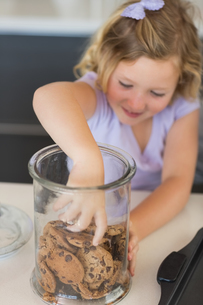 Girl reaching for cookies in jar FYI00000768