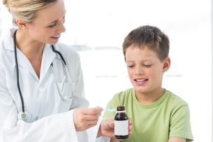 Pediatrician giving little boy syrup FYI00000875