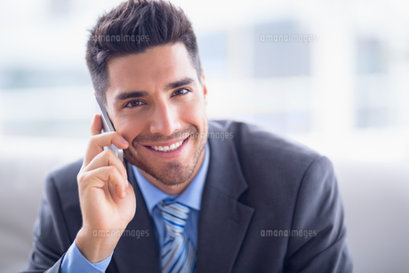 Handsome businessman sitting on sofa making a call smiling at camera FYI00000903