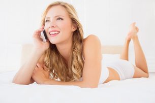 Happy young blonde on the phone lying on bed FYI00000971