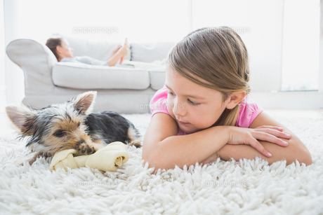 Little girl lying on rug with yorkshire terrier FYI00001083
