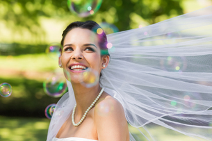 Beautiful bride looking at soap bubbles in park FYI00001120