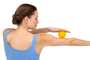 Rear view of a young woman holding stress ball on arm FYI00001620