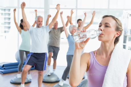 Woman drinking water with people stretching hands at fitness studio FYI00001776