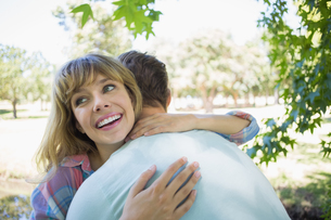 Pretty blonde smiling in a park while hugging boyfriend FYI00001966