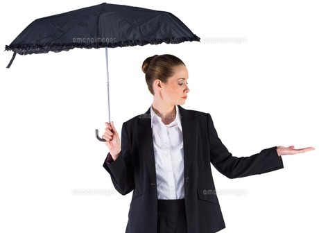 Businesswoman holding a black umbrella FYI00002019
