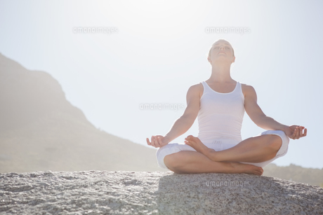 Blonde woman sitting in lotus pose on beachの素材 [FYI00002046]