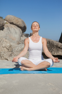 Blonde woman sitting in lotus pose on beach on mat FYI00002048
