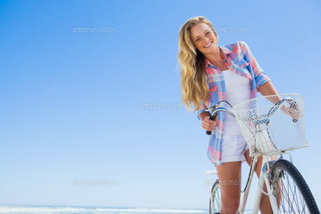 Pretty blonde on a bike ride at the beach smiling at camera FYI00002061