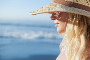 Gorgeous blonde in straw hat smiling on beach FYI00002063