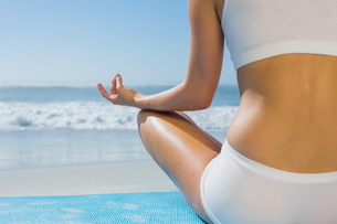 Fit woman sitting in lotus pose on the beach FYI00002080