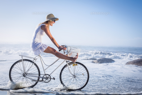 Gorgeous happy blonde on a bike ride at the beach FYI00002084