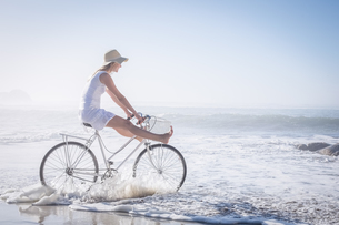 Gorgeous happy blonde on a bike ride at the beach FYI00002089