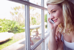 Pretty blonde sitting by the window on a phone call FYI00002096