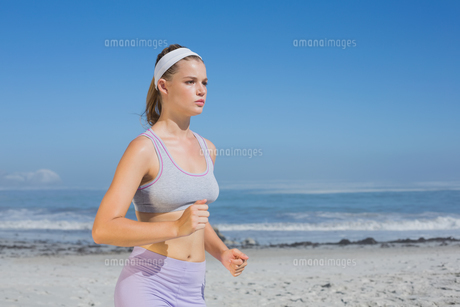 Sporty focused blonde jogging on the beach FYI00002132